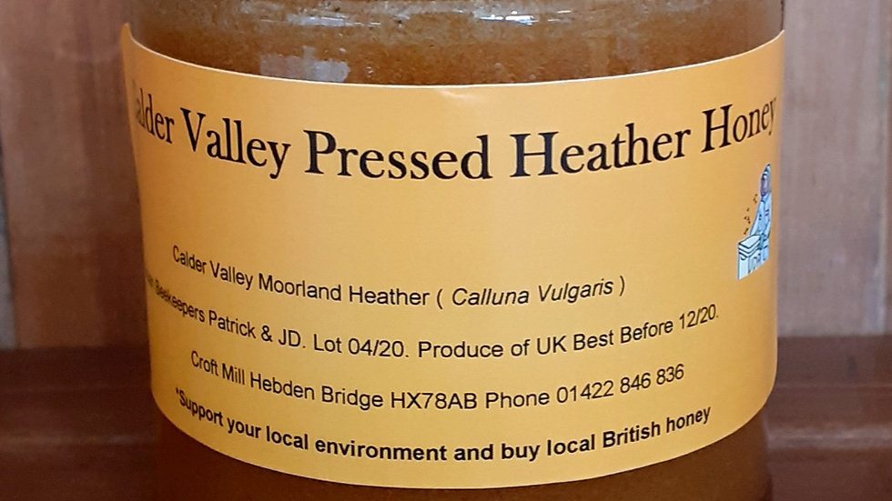 a jar of local heather honey with an orange label with text on wooden shelf