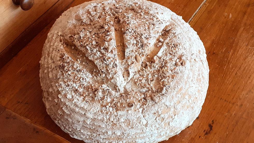 a seedy polish rye bread on a wooden shelf