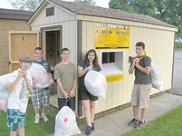 kid volunteers in front of new clothing shed