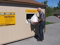 older gentlemen donating clothing into shed