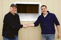 two men shaking hand after installing new shed