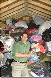 man smiling with pile of clothing donated
