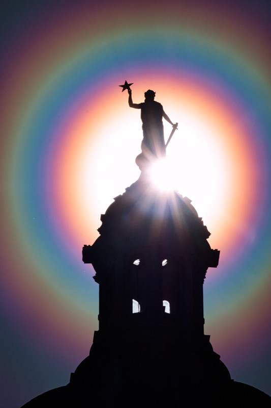 Standing at the top of the Texas Capitol Dome, the Goddess of Liberty is surrounded by a rainbow pollen corona.