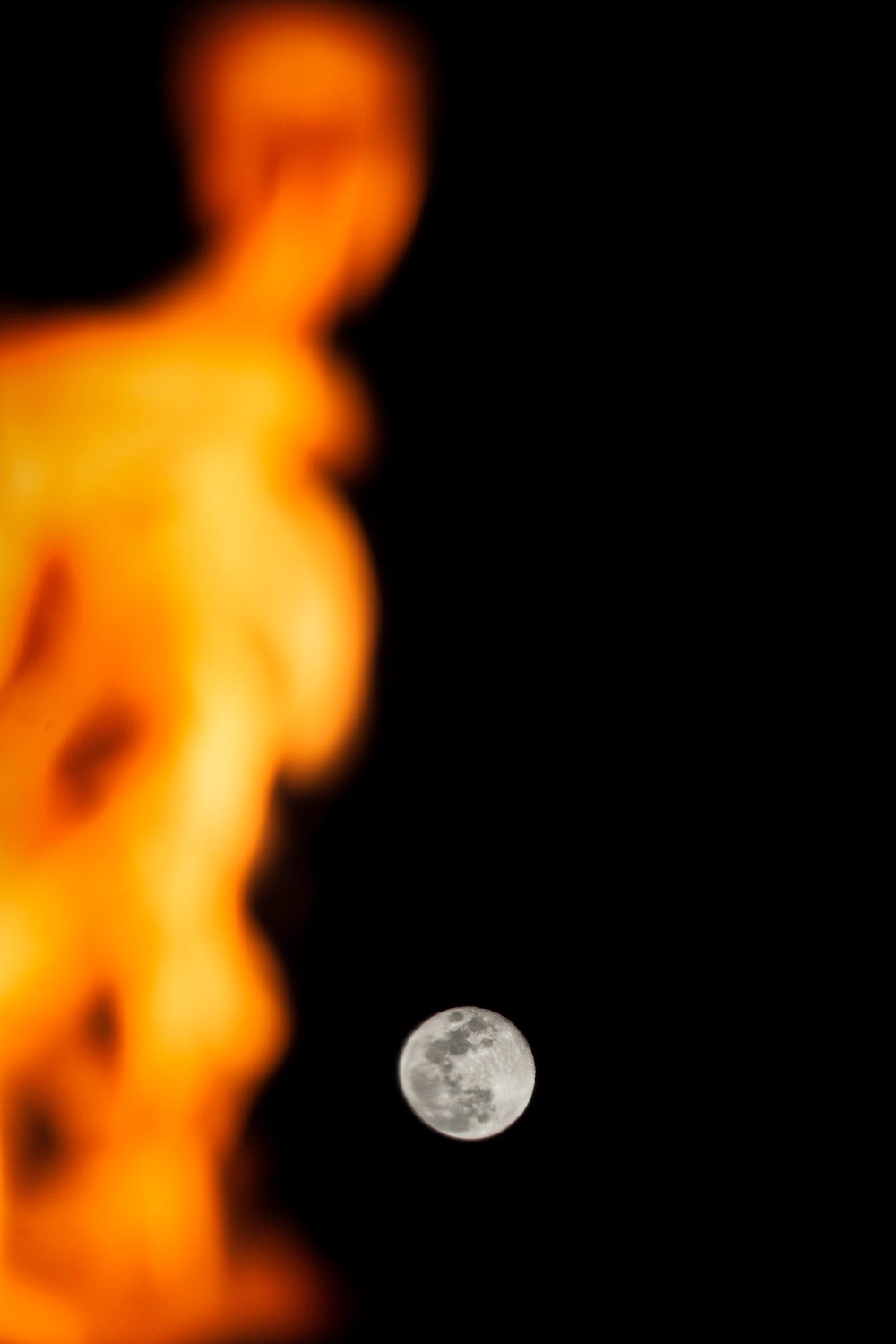 Full moon and a tiki torch fire