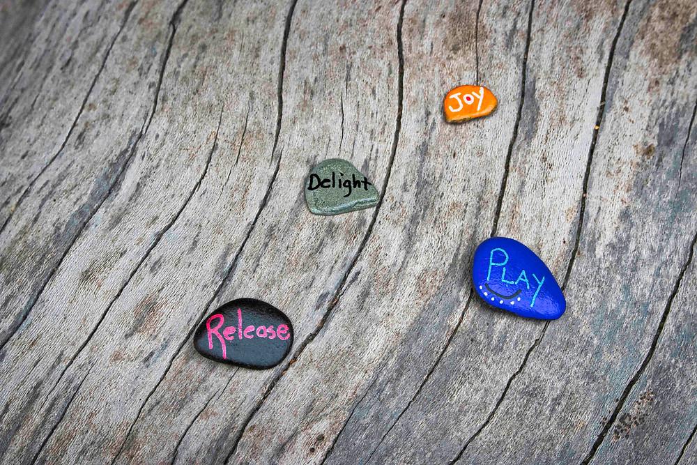 painted rocks on a fallen log