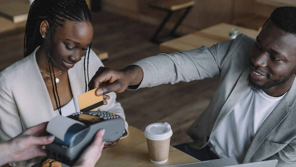 Deux personnes en train d'effectuer une transaction avec une carte bancaire. Courtoisie photo: Canva