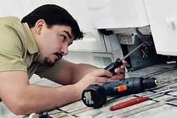 repairman working on dishwasher repair