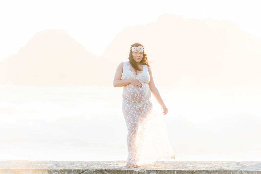 Pregnant woman standing at Sutro Baths wearing lace dress