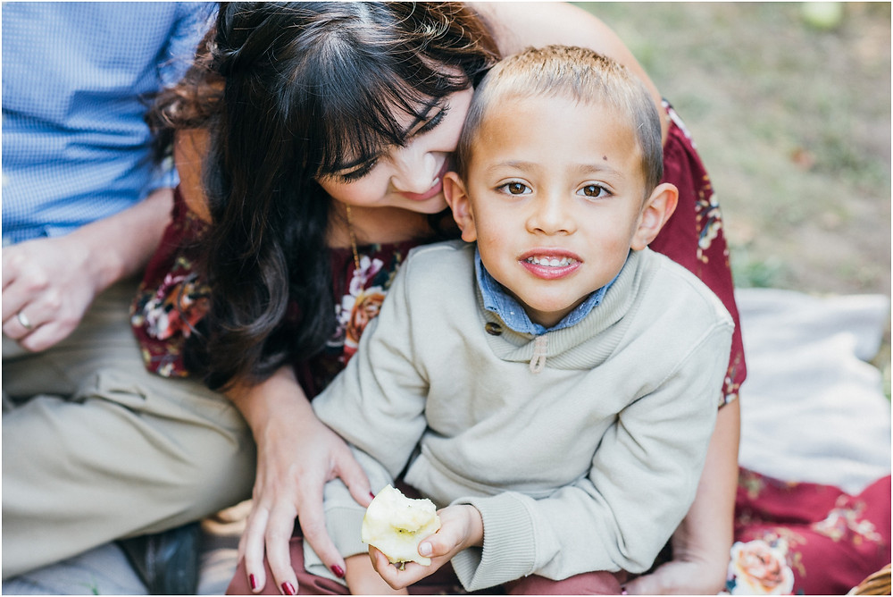 little boy eating apple while sitting in moms lap, bay area photographer