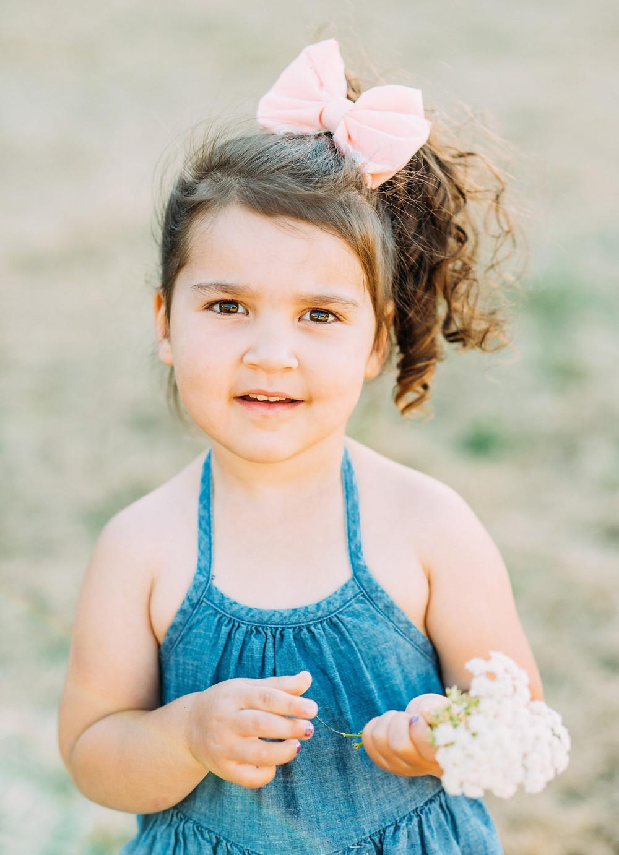 Little girl in denim romper smiling at camera in San Jose
