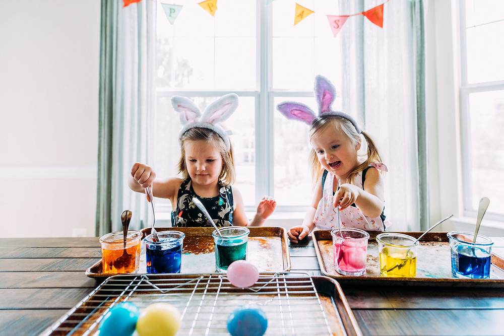 Two little girls dying Easter eggs while wearing bunny ears