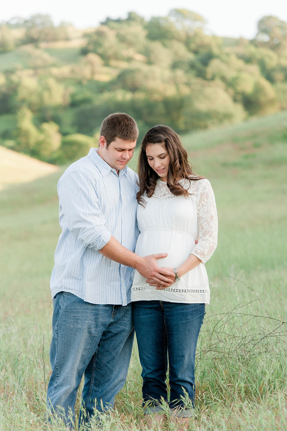 Couple standing in field for maternity photos in San Jose