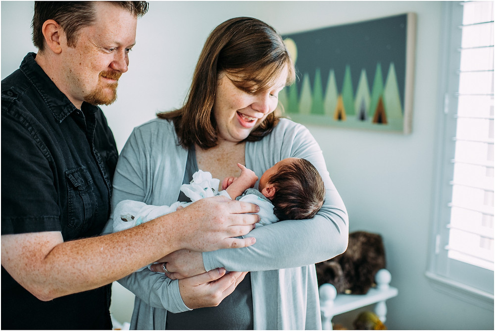 Mom & Dad holding newborn for lifestyle session in Bay Area, Ca