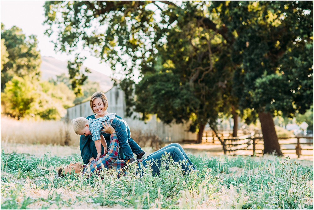 Dad lifting little boy while laying in flower field in front of a rustic barn for maternity photos
