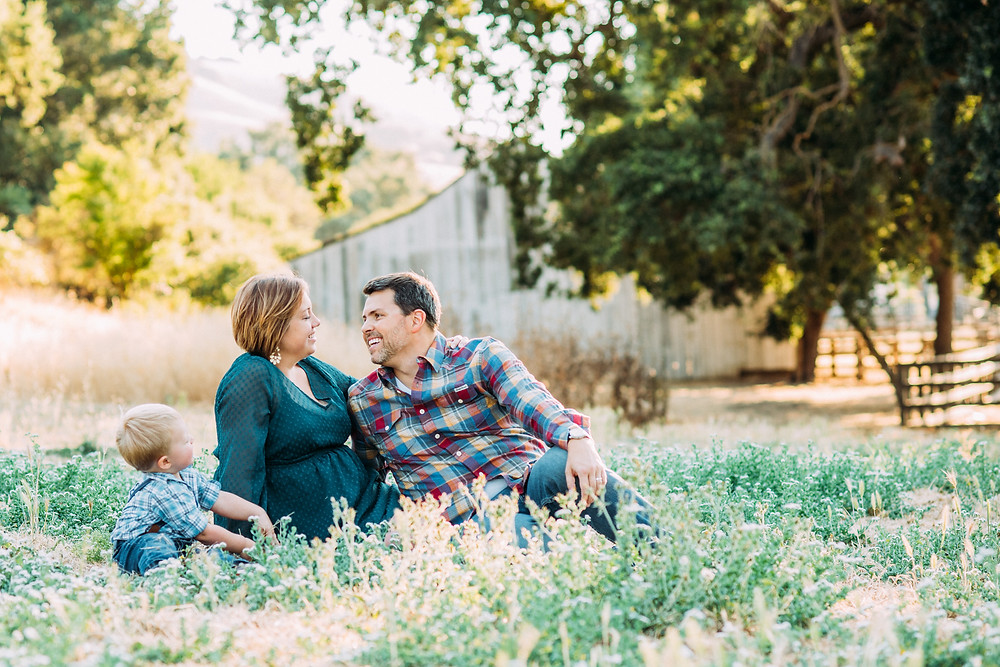 Family photographer in front of old barn in San Jose