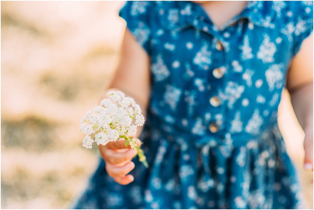 Little girl holding white flowers in hands