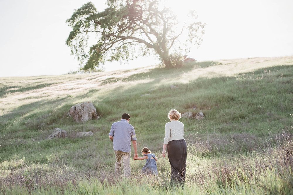 Family walking up rolling green hills with oak trees