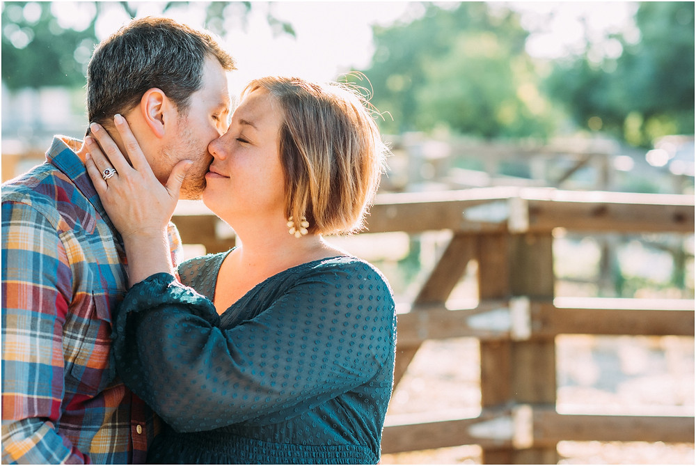 Mom kissing dad's cheek in front of fence for maternity pictures in San Jose, ca