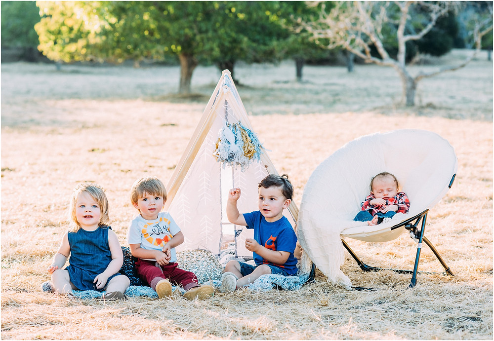 4 kids sitting in teepee during golden hour session in Portola Valley