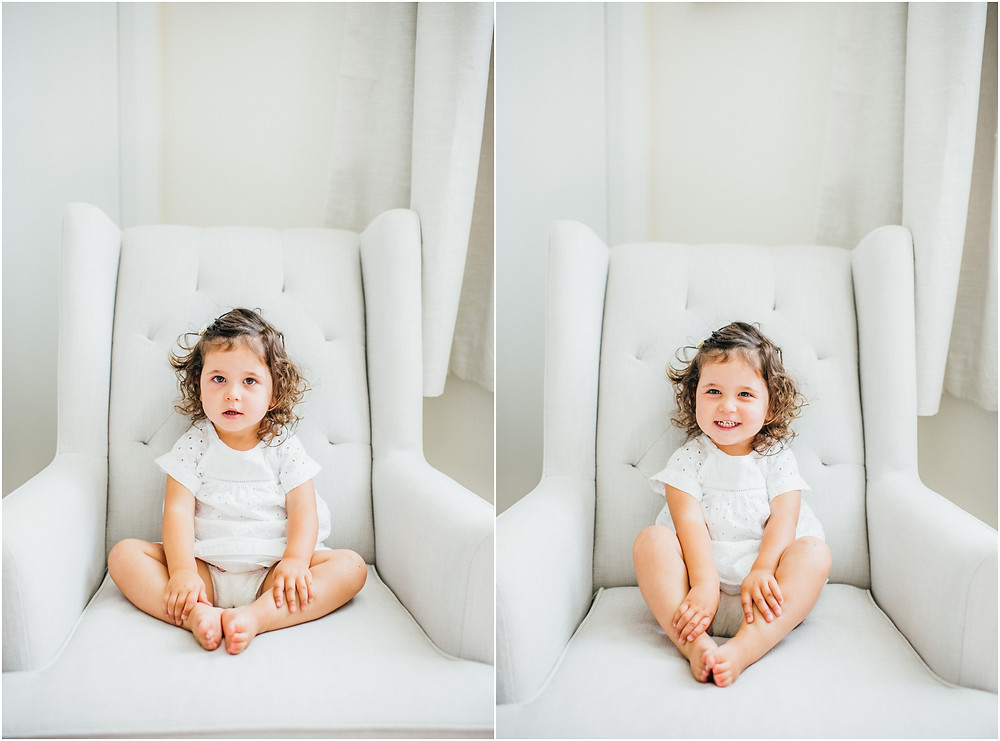 Toddler smiling in Pottery Barn rocker