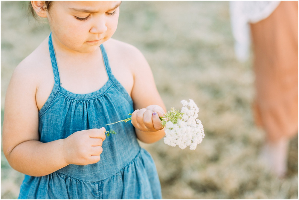 Little girl looking at white flowers she just picked