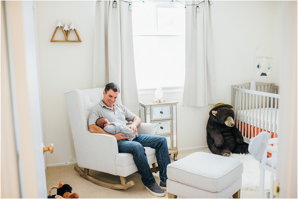 Dad rocking baby in his nursery