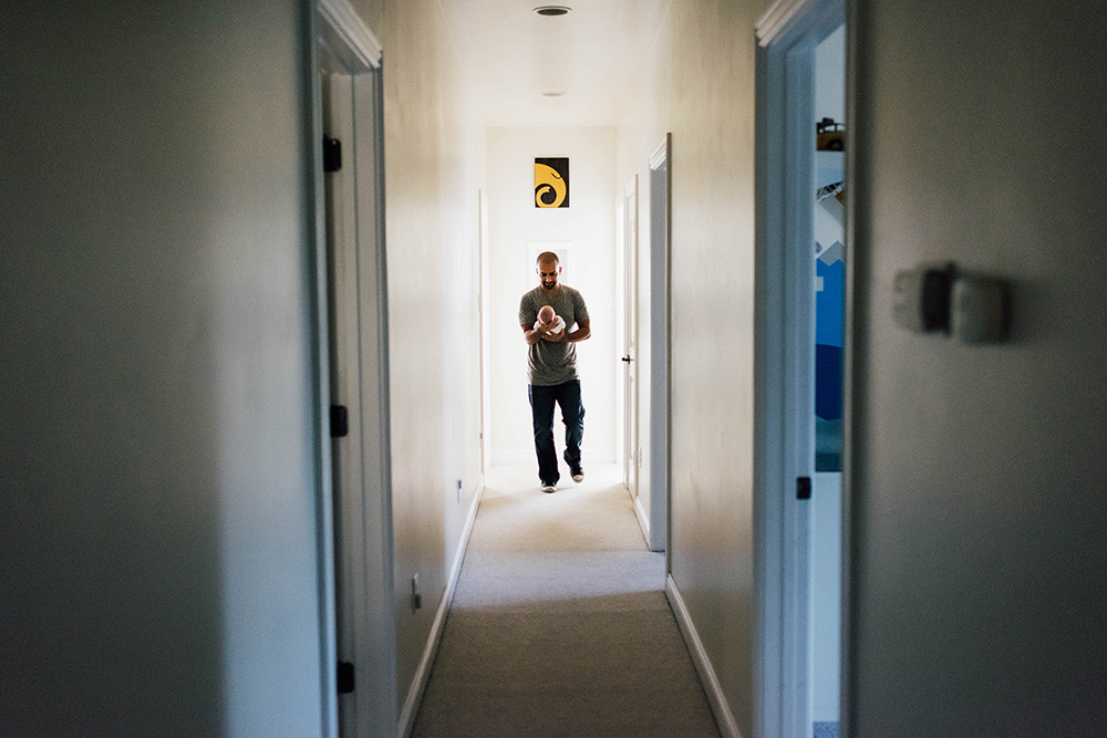 Dad walking down long hallway with his newborn in his hands