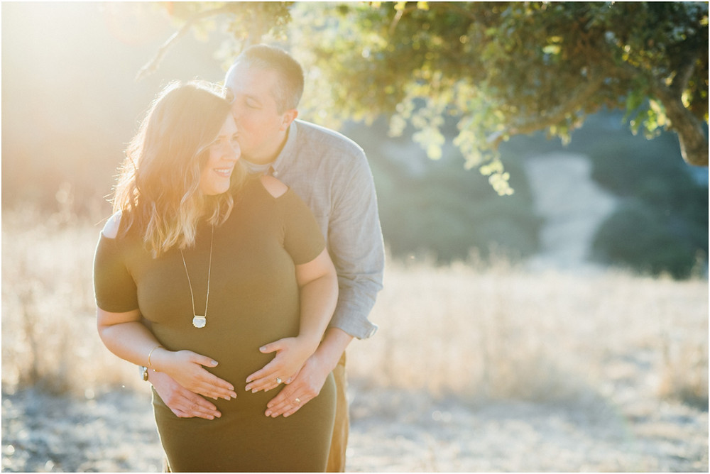 Husband kissing his wife during maternity session in the Bay Area