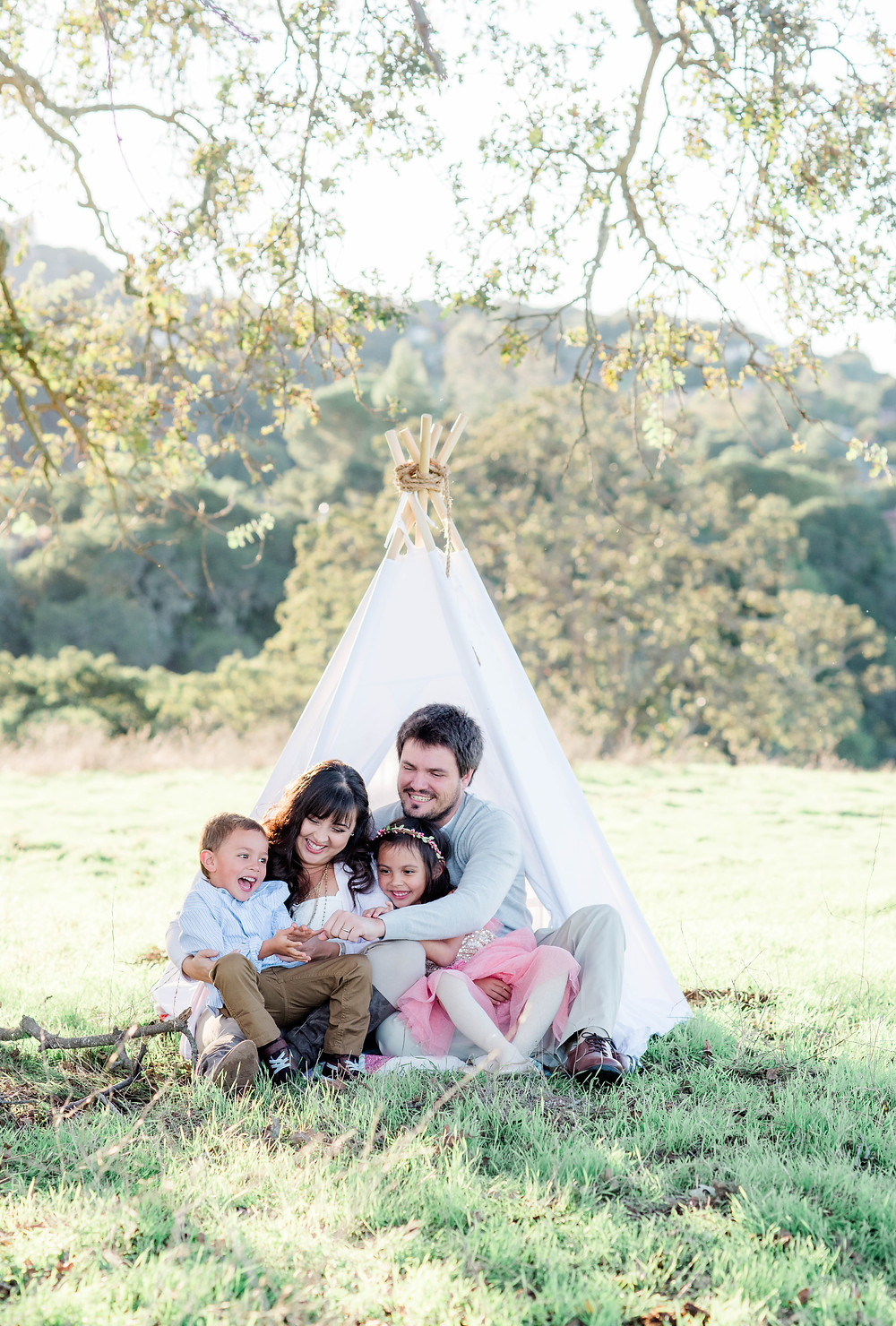 Family tickling little brother under oak tree in a teepee in Palo Alto