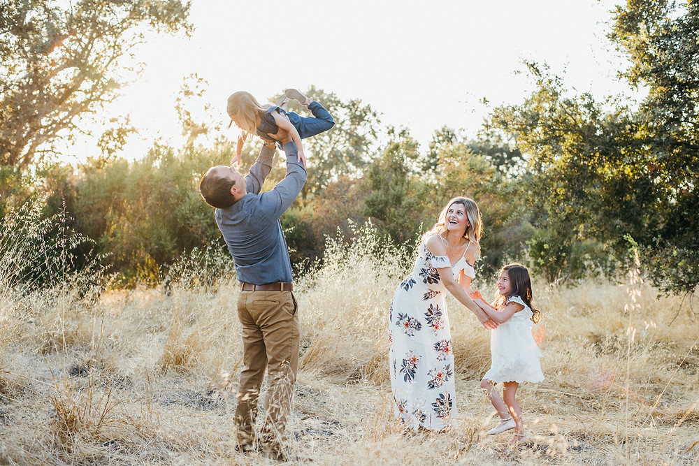 Family playing during golden hour in San Jose. Daddy lifting daughter in the air.