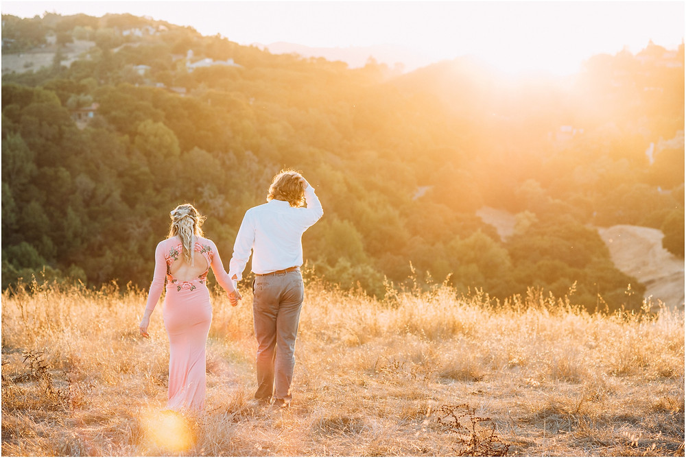 Couple walking in field at sunset in Los Altos, Ca