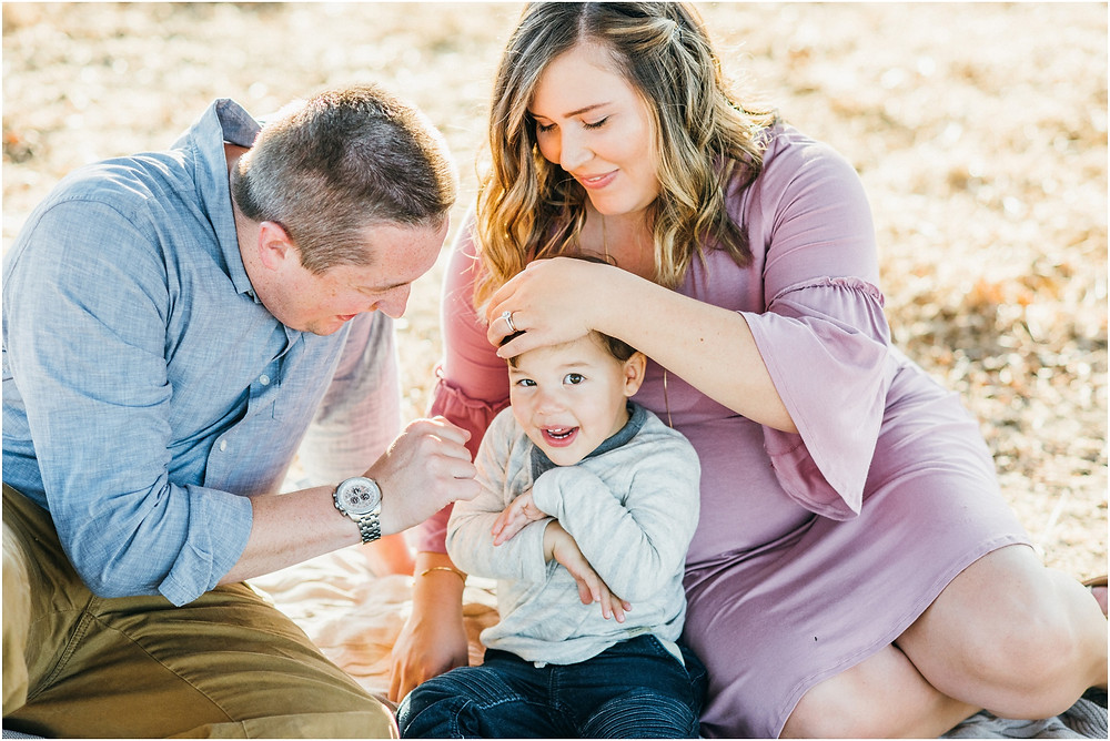 Little boy being tickled by dad during family photo session in Bay Area