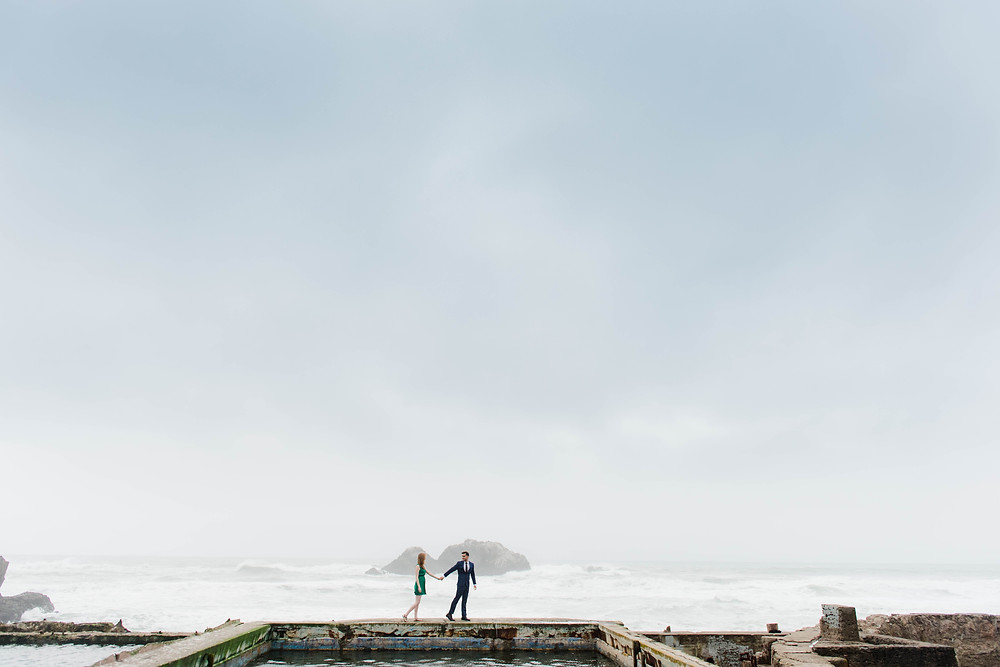 Wide angle shot of couple standing at Sutro Baths in San Francisco