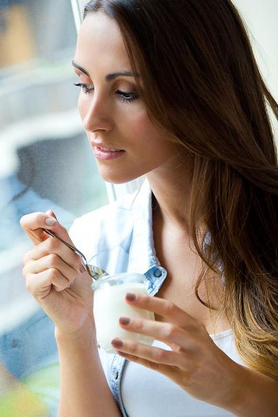 joven-mujer-casa-comiendo-yogur_1301-531