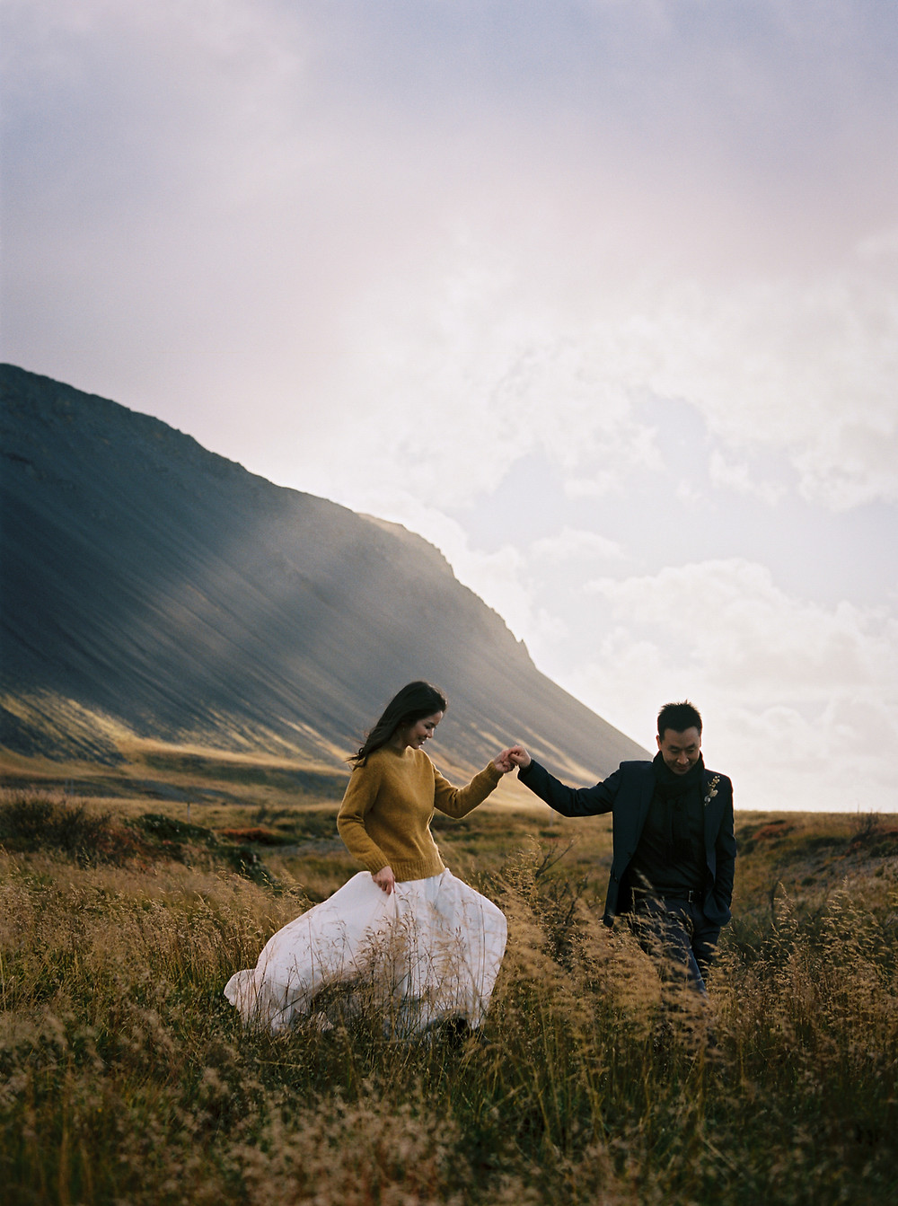 Cosy fall wedding in Iceland / Wedding couple in front of Icelandic mountain landscape / Intimate Iceland elopement