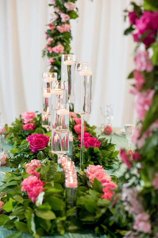 Lush greens and roses accented with floating tea lights