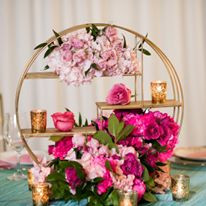 Tiered centerpiece surrounded by layers of fresh florals and candlelight.