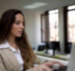 Mulher executiva em frente ao computador, realiza sessão de coaching executivo remoto.