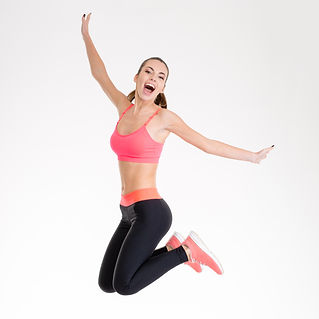 Happy joyful young fitness woman in pink top and black leggings jumping over white background.jpg