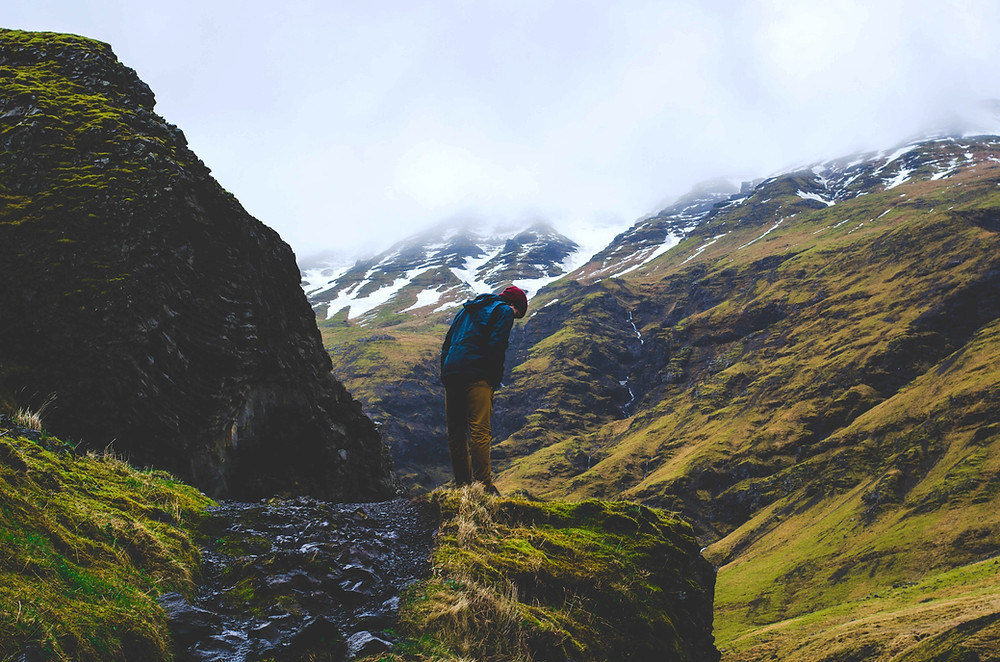 Man looking over cliff edge in fjord in Iceland