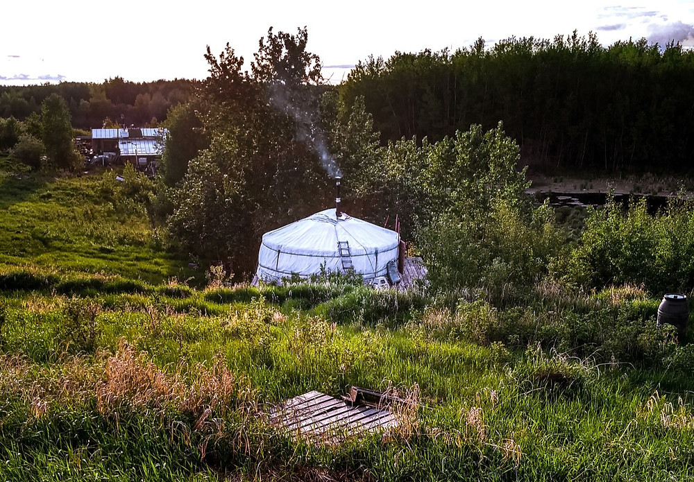 A yurt with smoke billowing from the chimney, surrounded by trees and grass.