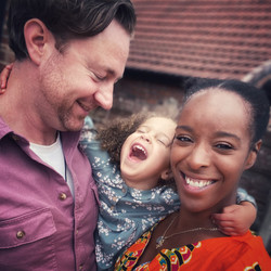 White dad with black mum holding laughing mixed race child