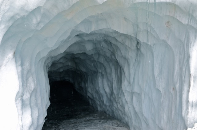 Massive and inviting, an ice-tunnel digs deep beneath the glaciers above it