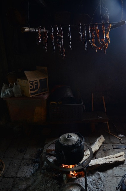 Inside a local kitchen with strips of pork hanging above the fire pit. Regardless of the money that flows in many areas remain simple and traditional