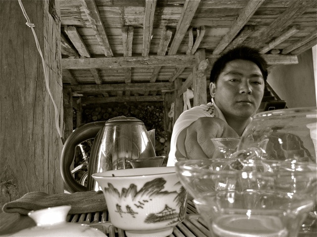 Dafa hovers over his little tea table. A full 80% of Dafa's home is committed to the leaf that the Hani call 'la' - tea