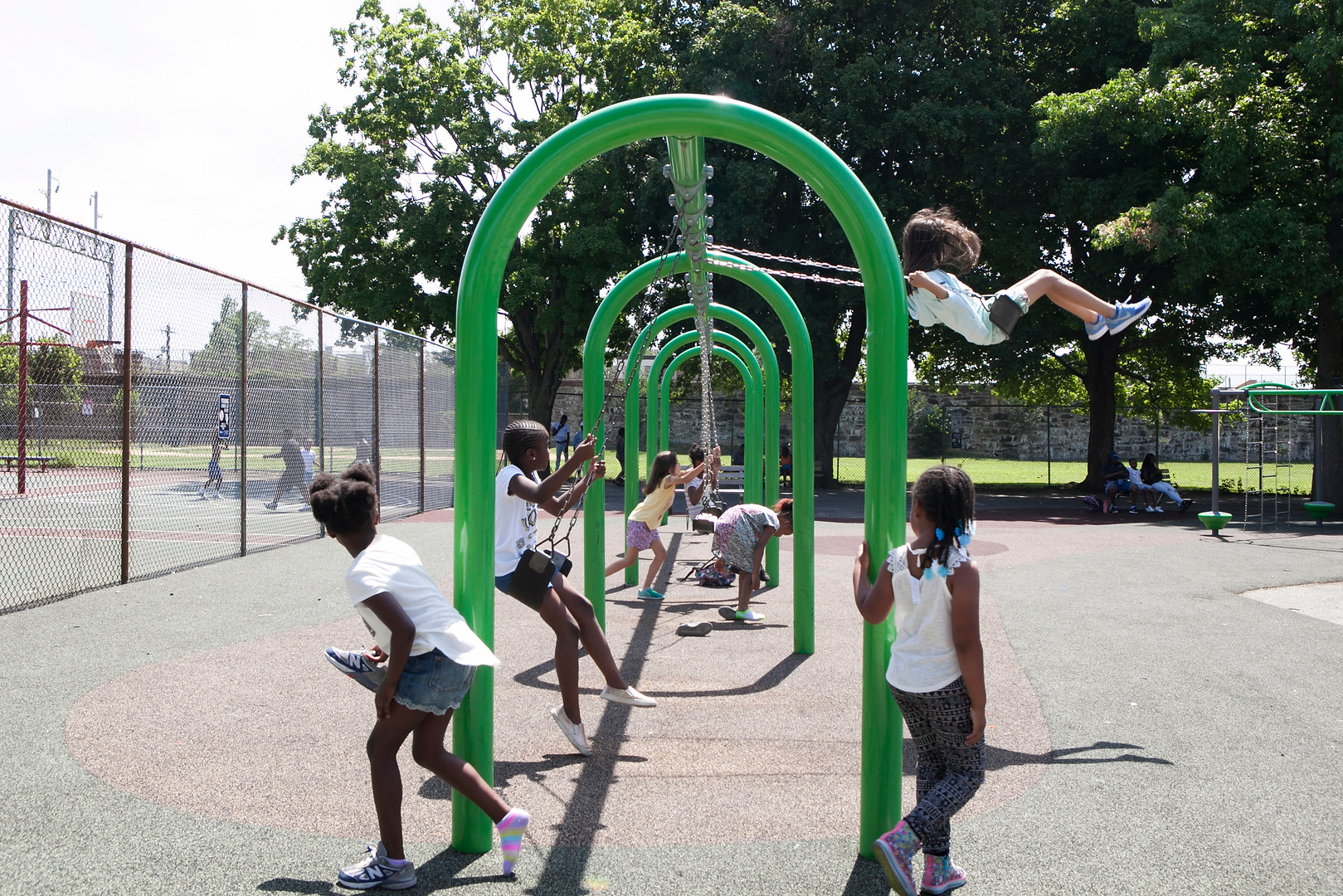 Kids from R.W. Brown Summer Camp play on the swings at Dendy Recreation Center at 10th and Oxford Streets in North Philadelphia on the morning of Friday, June 29, 2018. Maggie Loesch / WHYY