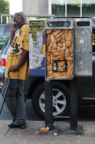A man stands against pay phones stuffed with old hoagie rolls on Broad Street and Cecil B. Moore Avenue in North Philadelphia on Sept. 22, 2017.  Maggie Loesch / Personal