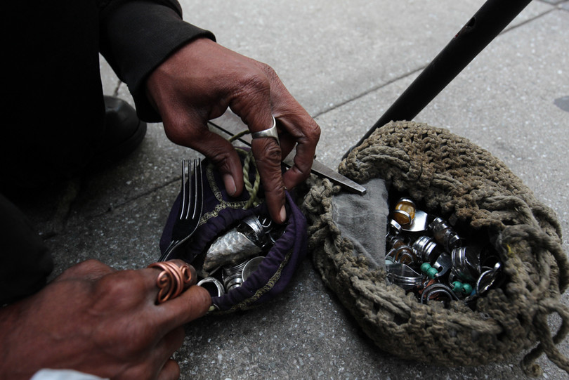 """Searching through his pouch of gem-stones, Williams describes how he crafts jewelry out of silverware. """"I order all the stones off Amazon,"""" he said. """"I use pliers to bend the fork or spoon, sometimes I need to file it down. I add the stone and shape [the silverware] around it, then it's done."""""""