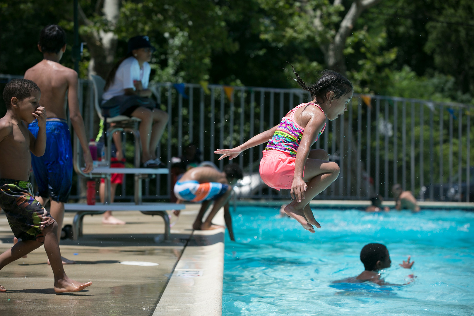 Ariana Reyes, 6, does a cannonball into the Pyne Poynt Park Pool in North Camden to celebrate the opening of city pools for the season on the afternoon of June 29, 2018.  Maggie Loesch / The Philadelphia Inquirer