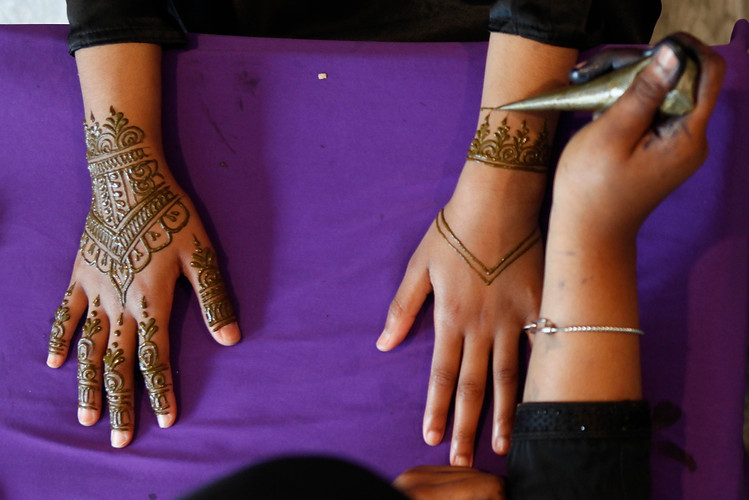 Hind Canty draws henna designs on a client's hands in preparation for Eid al-Fitr on the afternoon of Wednesday, June 13, 2018. Eid, as it is called colloquially, signals the end of Ramadan and is an important religious holiday for the Muslim community.  Maggie Loesch / The Philadelphia Inquirer